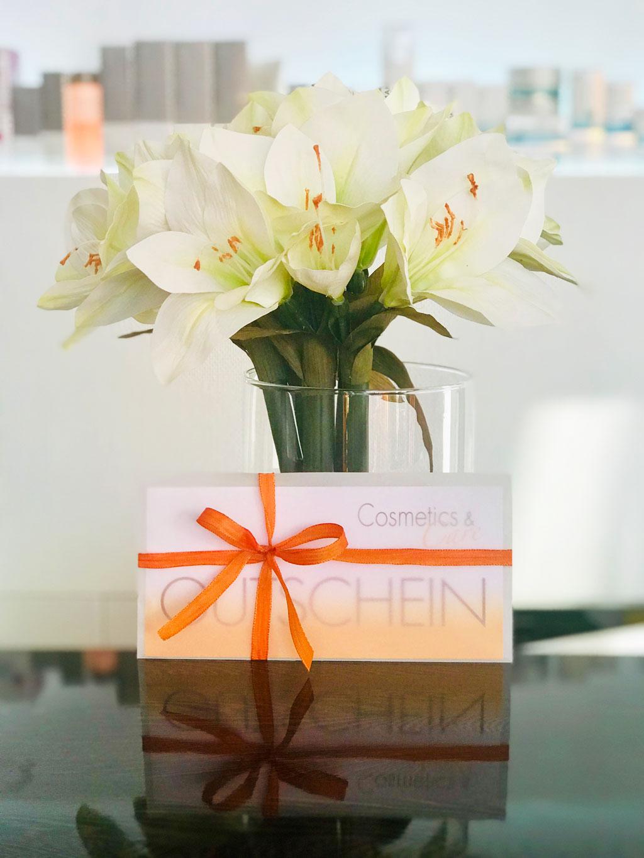 Ein Cosemtics & Care Gutschein verpackt in einen transparenten Umschlag mit einem Schleifchen steht angeleht an eine Blumenvase auf der Theke des Kosmetikstudios